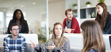 un groupe de plusieurs professionnels hommes et femmes discutent des avantages de l'alternance