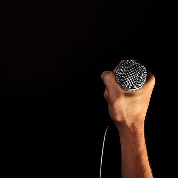 une main tient un micro de journaliste sportif sur fond noir