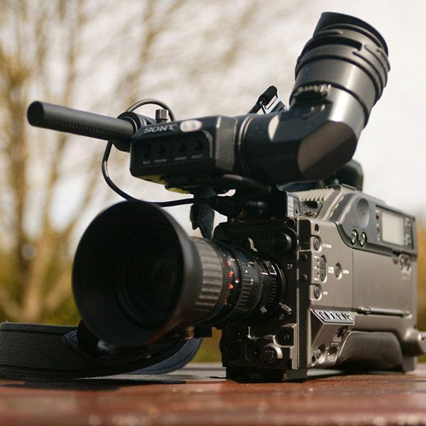 une caméra professionnelle de journaliste sportif est posée sur un table en extérieur
