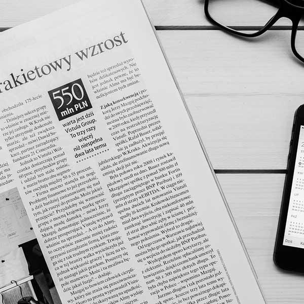 page d'un journal, un smartphone et des lunettes de journaliste sur une table en bois blanc