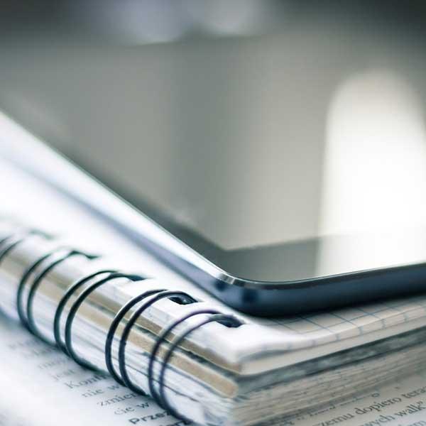 une tablette posée sur un cahier à spirale pour réviser son Master Journalisme sportif de l'IICP