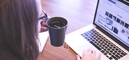 une étudiante travaille son Master Communication Digitale avec son ordinateur portable et sa tasse de café